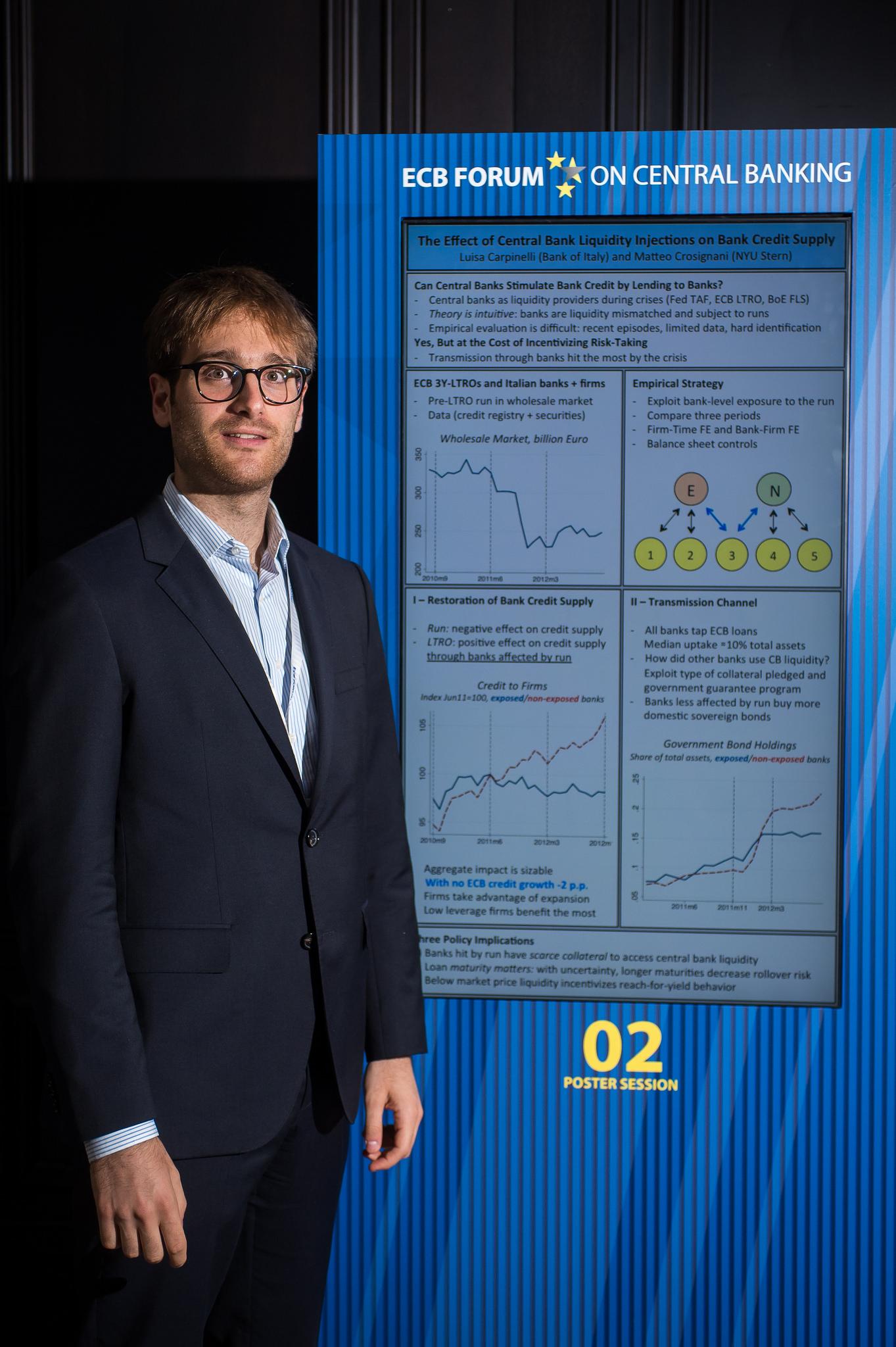 economista italiano Matteo Crosignani davanti al poster che illustra la sua ricerca, vincitrice del Premio della Banca Centrale Europea